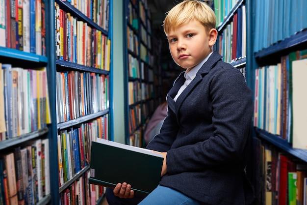 Erudycki chłopiec siedzący wśród książek w bibliotece między półkami, w poszukiwaniu najciekawszej książki, poważnie patrzy w kamerę
