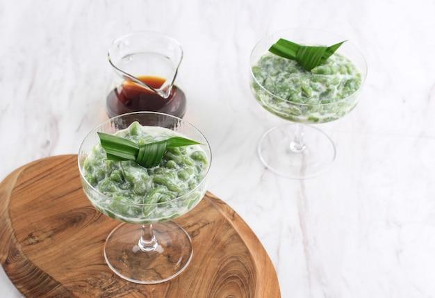 Es cendol ijo lub dawet to tradycyjny mrożony deser z indonezji zrobiony z mąki ryżowej, cukru palmowego, mleka kokosowego i liści pandan dla aromatów. podawane w wysokim szkle. popularny podczas śniadania w czasie ramadanu.
