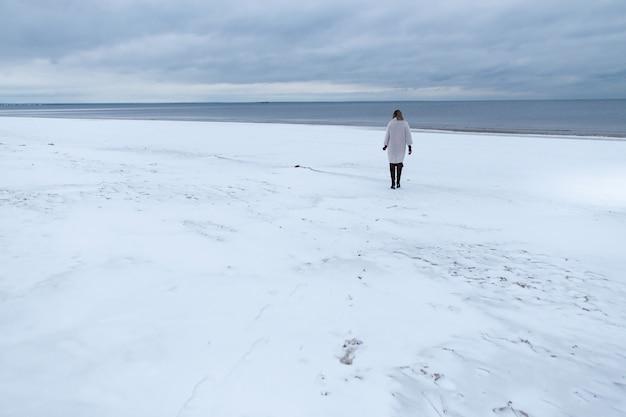 Eskapizm, koncepcja relaksu natury. samotna dziewczyna w płaszczu na tle zimowego morza. portret kobiety na morzu, wietrzna pogoda, zimny obraz atmosferyczny.