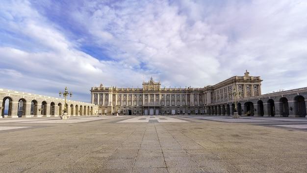 Esplanada i duży dziedziniec pałacu królewskiego w madrycie o wschodzie słońca w dzień z błękitnym niebem i chmurami. hiszpania.