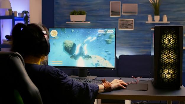 Esportowa gra wideo r nosząca zestaw słuchawkowy i grająca w grę wideo online o mistrzostwo strzelców kosmicznych