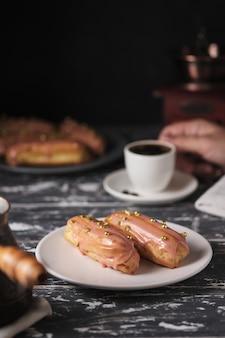 Espresso i eklery na śniadanie. smaczne torty na drewnianym stole w kuchni.