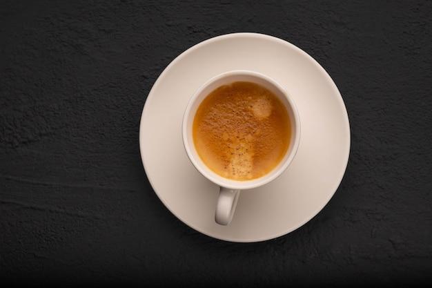 Espresso w białej filiżance na ciemnym tle