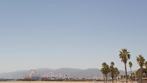 Estetyczna plaża w kalifornii, diabelski młyn na molo i palmy w santa monica, los angeles, usa