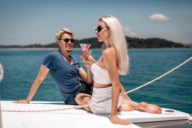 Estetyczne młode i atrakcyjne modelki o blond włosach bawiąc się na świeżym powietrzu, trzymając koktajle w kryształowych kieliszkach.