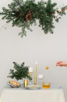 Estetyczny wzór na boże narodzenie z wiszącą girlandą sosnową nobilis, świecami i dekoracjami stołu. wysokiej jakości zdjęcie