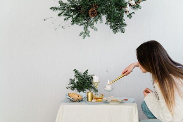 Estetyczny wzór na boże narodzenie z wiszącą girlandą sosnową nobilis, świecami i dekoracjami stołu.