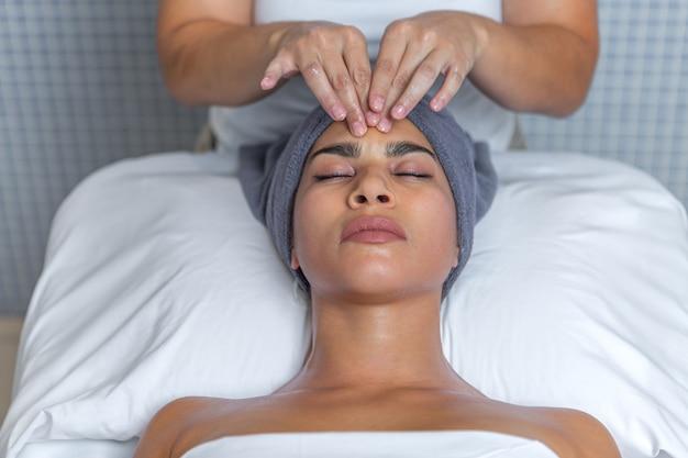 Estetyk daje masaż twarzy kremem na zrelaksowanej kobiecej twarzy w spa. koncepcja pielęgnacji skóry.