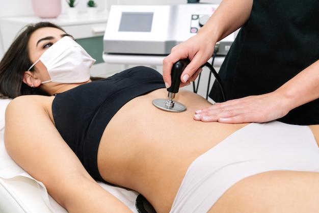 Estetyk udzielający kobiecie zabiegu o częstotliwości radiowej w żołądku, który stymuluje prawidłowe funkcjonowanie komórek