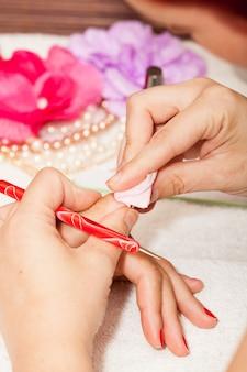 Estetyk usuwa stary lakier do paznokci bawełną i zmywaczem