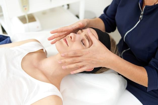 Estetyk wykonujący profesjonalny masaż twarzy na twarzy kobiety w klinice spa. masaż przeciwstarzeniowy liftingujący twarz. profesjonalny masaż drenażu limfatycznego w klinice spa