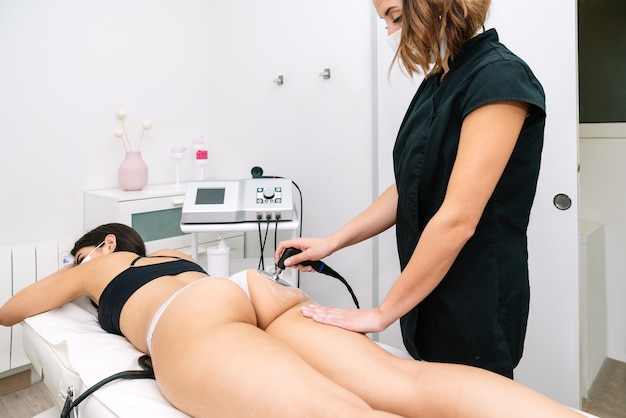 Estetyk wykonujący zabieg fal radiowych kobiecie w pośladki, który stymuluje prawidłowe funkcjonowanie komórek