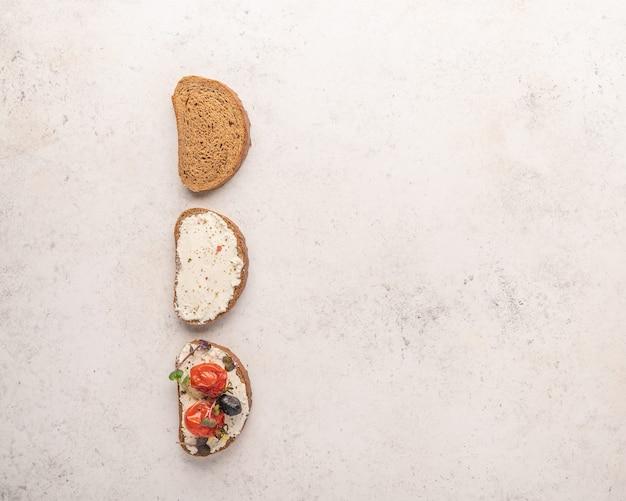 Etapy robienia kanapki z chleba, sera ricotta, solonego łososia, pieczonych pomidorów i zieleniny na jasnej przestrzeni