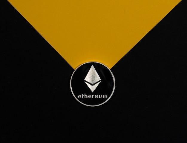 Ethereum lub srebrna moneta eth na czarno-żółtym tle kryptowaluta i koncepcja krypto etherum