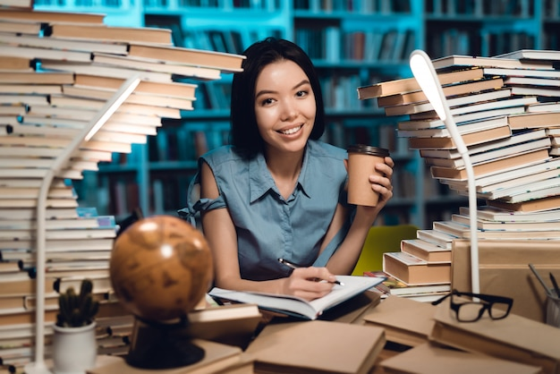Etniczna azjatykcia dziewczyna otaczająca książkami w bibliotece. student pisze w zeszycie.