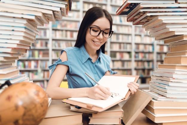 Etniczna azjatykcia dziewczyna pisze w notatniku.