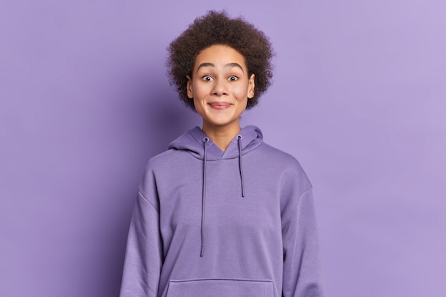 Etniczna dziewczyna z włosami afro uśmiecha się przyjemnie i wygląda ciekawie, nosi bluzę z kapturem.