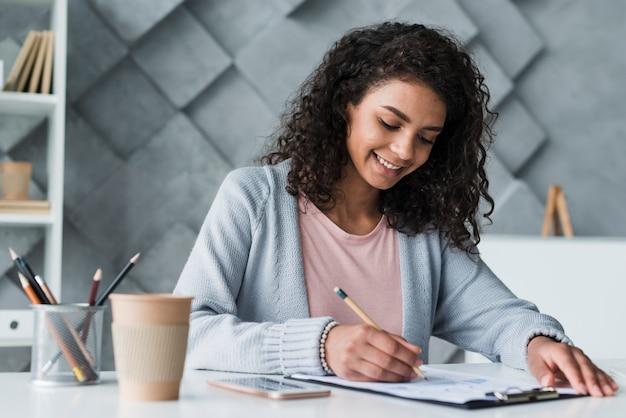 Etniczna kobieta pracuje przy biurkiem w biurze