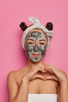 Etniczna kobieta ze spa nosi maskę kosmetyczną na twarzy, kształtuje serce na ciele, wyraża miłość, wykonuje zabiegi przeciwzmarszczkowe po kąpieli, odizolowana na różowej ścianie. koncepcja piękna i wellnes