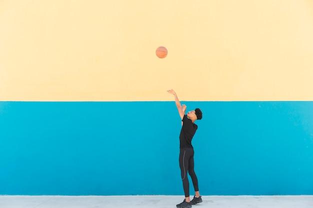 Etniczne baskeball gracz rzuca piłkę