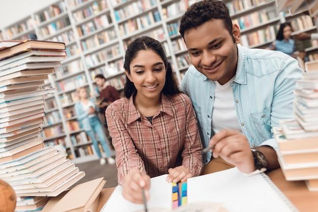 Etniczne indian mieszanej rasy dziewczyna i facet siedzi w bibliotece.