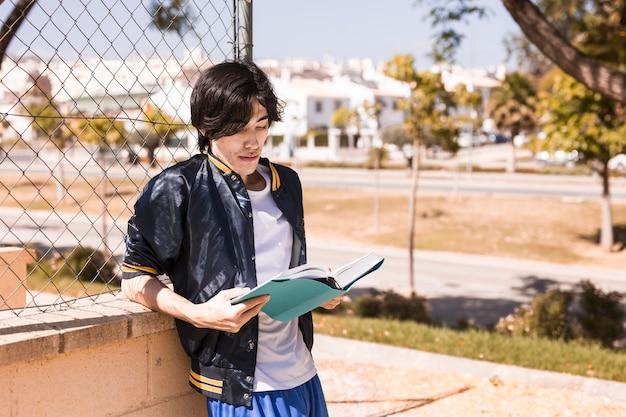 Etniczne uczeń stojący czytanie książki