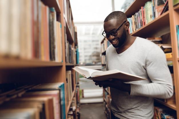 Etnicznego amerykanina afrykańskiego pochodzenia faceta czytelnicza książka w bibliotece.