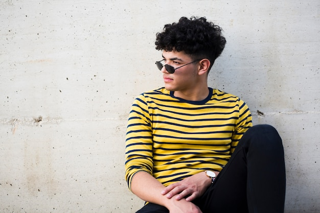Etniczny elegancki młodzieniec w pasiastej jaskrawej koszula i okularach przeciwsłonecznych
