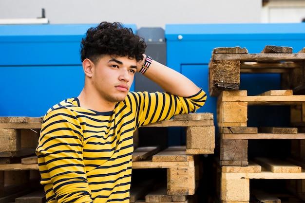Etniczny kędzierzawy mężczyzna oparta ręka na drewnianych paletach