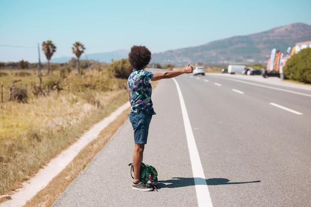 Etniczny mężczyzna autostopem na poboczu drogi