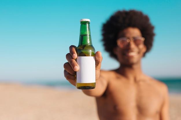 Etniczny mężczyzna trzyma butelkę piwo