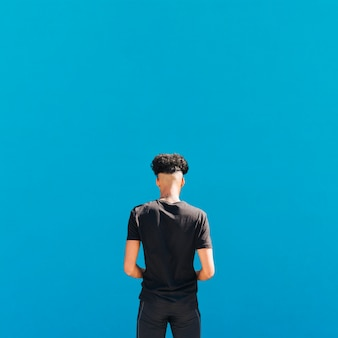 Etniczny sportowiec w czarnej odzieży sportowej na niebieskim tle