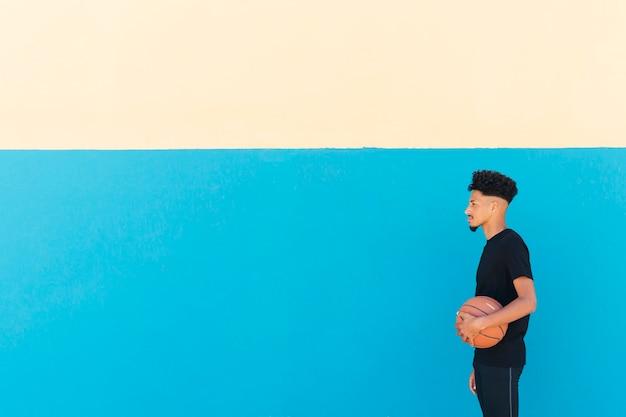 Etniczny sportowiec z kędzierzawego włosy pozycją z koszykówką