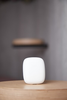 Etui na słuchawki bezprzewodowe leży na stole zamknięta pokrywa słuchawek tło jest rozmyte