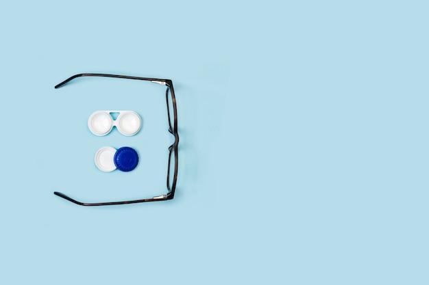 Etui na soczewki kontaktowe i okulary na niebieskim tle w widoku z góry