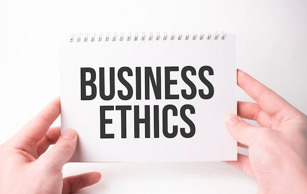 Etyka biznesowa napis słowny na białej kartce papieru w rękach mężczyzny