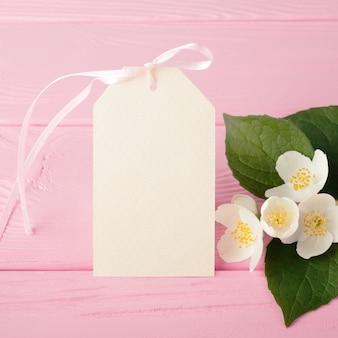 Etykieta i kwiaty jaśminu na pastelowym różu, pusta etykieta prezentowa.