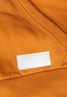 Etykieta na ubrania na pomarańczowej bluzie sportowej z bliska