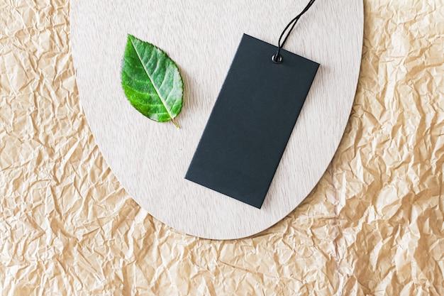 Etykieta odzieżowa i zielony liść jako ekologiczne tło flatlay zrównoważona moda i marka marki ko...