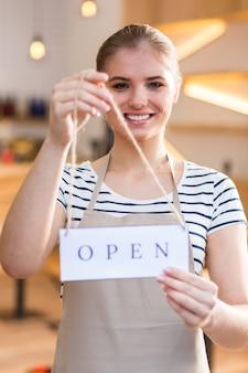 Etykieta tag. szczęśliwy pozytywny miła kobieta uśmiecha się i patrzy na ciebie mając etykietę w dłoniach