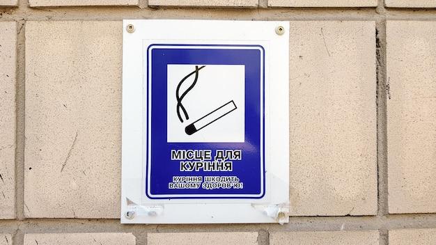 Etykieta z wizerunkiem papierosa w mieście z tekstem w języku ukraińskim. wyznaczenie strefy dla palących. oznaki palaczy, strefy ograniczonego palenia. ostrzeżenie, że palenie jest szkodliwe dla zdrowia.