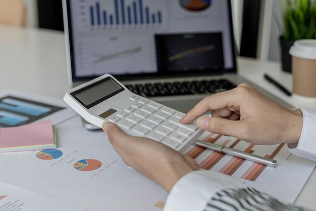 Etykietka księgowości naciska kalkulator, przelicza liczby z rachunku zysków i strat firmy oraz dokumentów finansowych, jest audytorem firmy. koncepcja audytu.
