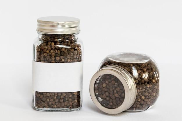 Etykietowane słoiki z asortymentem pieprzu czarnego