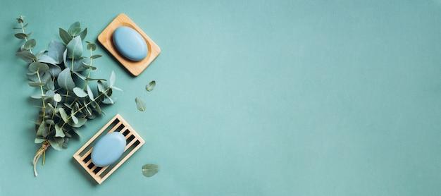 Eukaliptusowy istotny olej i mydło na zielonym tle. zero odpadów, naturalne organiczne narzędzia łazienkowe.