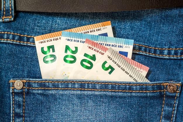 Euro pieniędzy banknoty w kieszeni niebiescy dżinsy zamykają up
