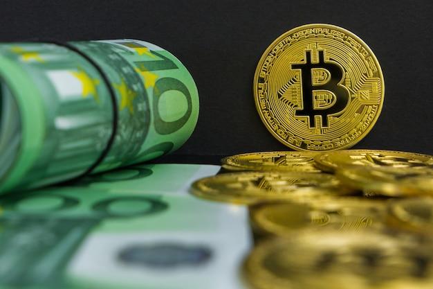 Euro vs kryptowaluta bitcoin. na czarnym jest sto banknotów euro i duże złote monety btc. złote bitcoiny nad euro
