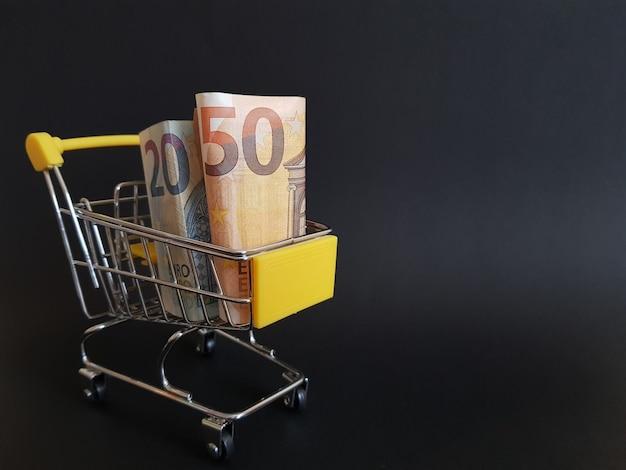 Euro w wózku z zabawkami na czarnym tle na białym tle