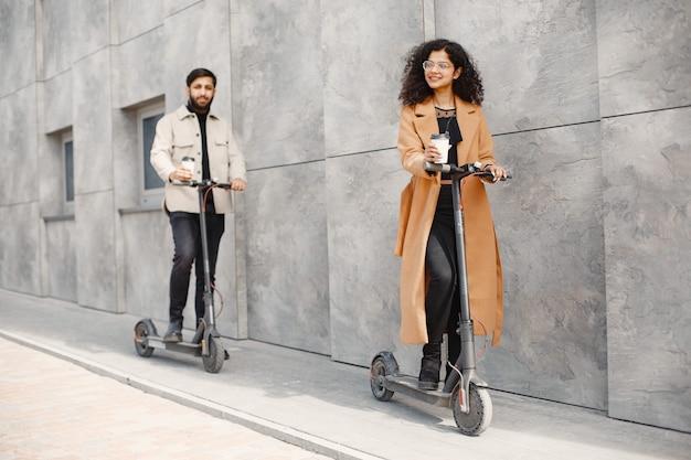 European girl anindian guy jeździć na skuterach i uśmiechać się. ludzie z kawą.