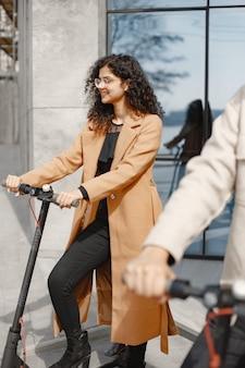 European girl anindian guy jeździć na skuterach i uśmiechać się.