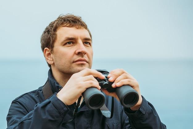 Europejczyk na morzu trzyma w rękach lornetkę, jego wzrok jest skierowany w górę